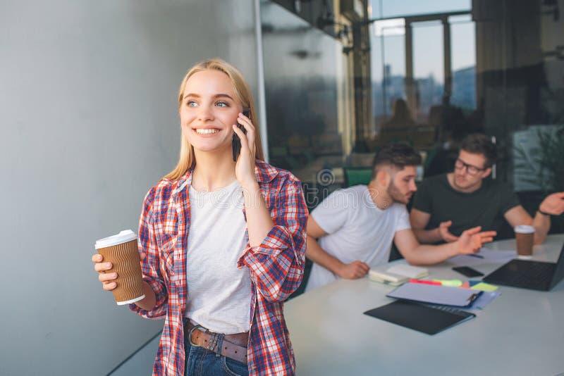 快乐的年轻女人立场和谈话在电话 她微笑 式样举行咖啡 两年轻人在她后坐在 免版税库存图片