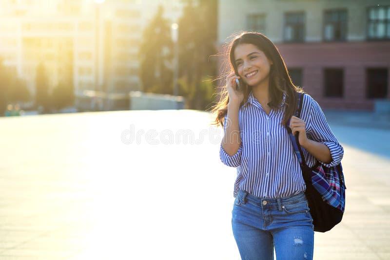 快乐的年轻女人谈话由电话户外与在她的面孔和拷贝空间的阳光 库存照片