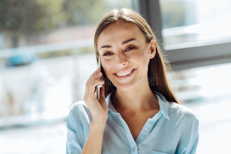 快乐的年轻女实业家谈话在她巧妙的电话 库存照片