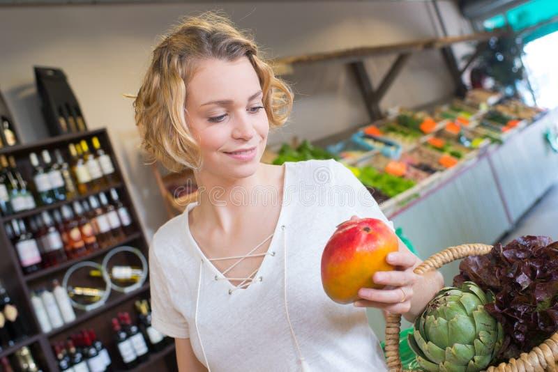 快乐的年轻女性在水果市场上的顾客买的芒果 库存图片