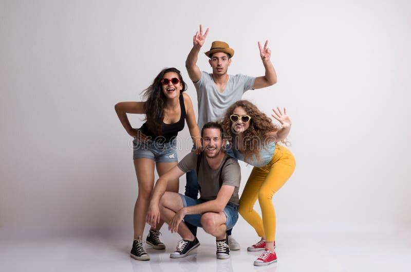 快乐的年轻小组画象有站立在演播室的帽子和太阳镜的朋友 免版税库存照片