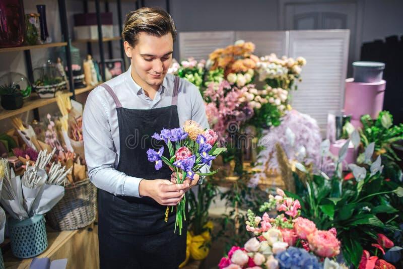 快乐的年轻男性卖花人举行五颜六色的花束在手上 他看它 不同的植物和花是在他后 库存照片