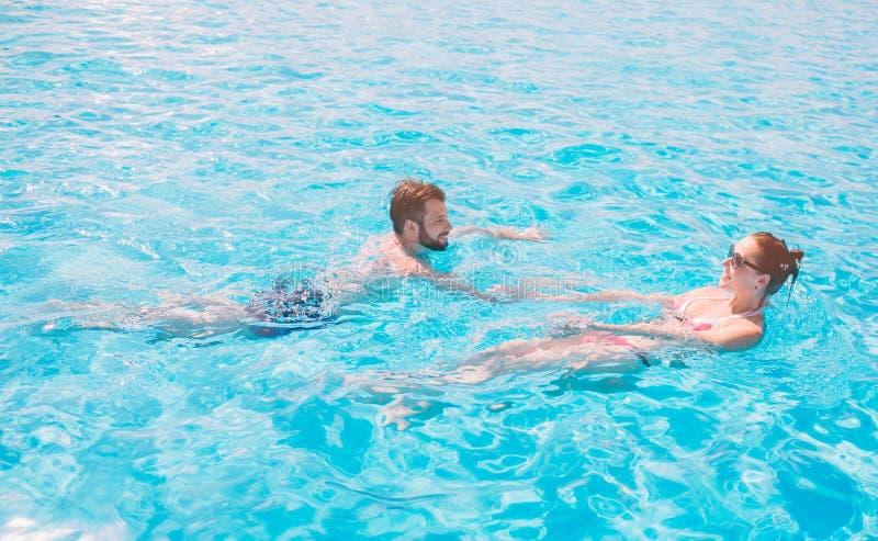 快乐的年轻的休息人和的夫人,当室外时的游泳池 夫妇在水中 人做夏天sephi 免版税库存图片