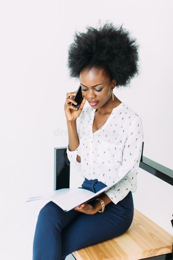 快乐的年轻美国黑人的女商人谈话在手机,坐椅子,隔绝在白色 免版税库存照片