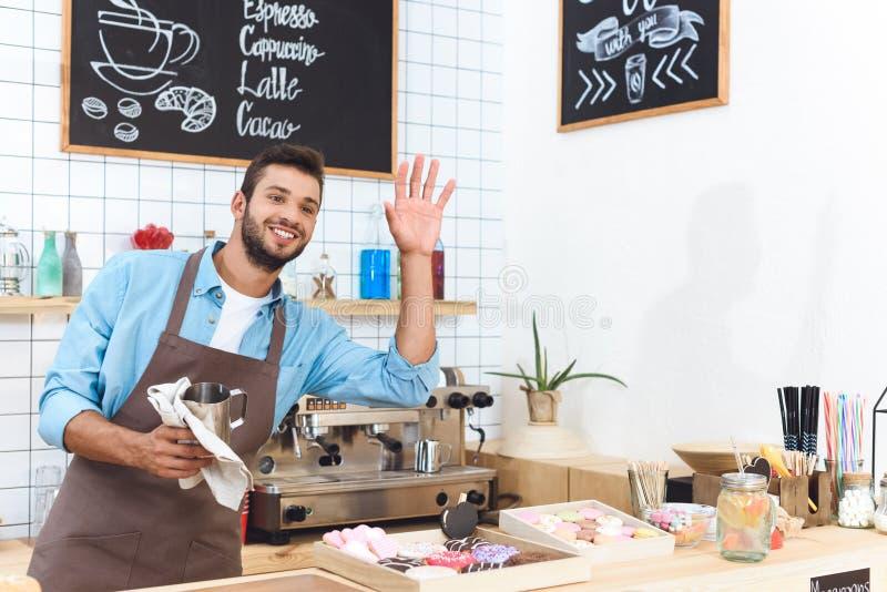 快乐的年轻barista清洁器物 免版税库存照片