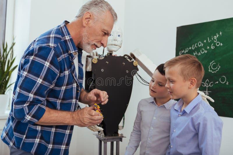 快乐的年迈的人谈话与他的学生 免版税库存图片