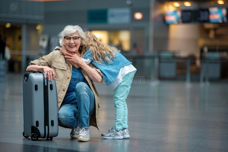 快乐的年迈的夫人和小女孩摆在与微笑 免版税库存图片
