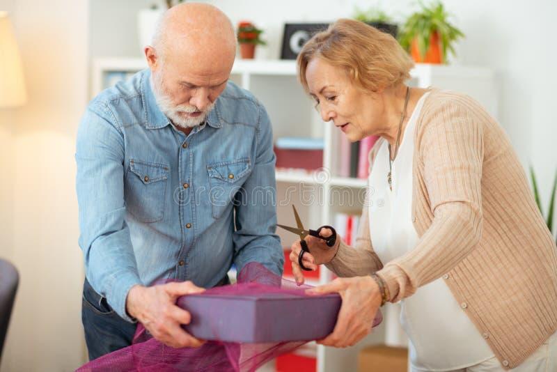快乐的年迈的妇女在她的手上的拿着剪刀 免版税库存照片