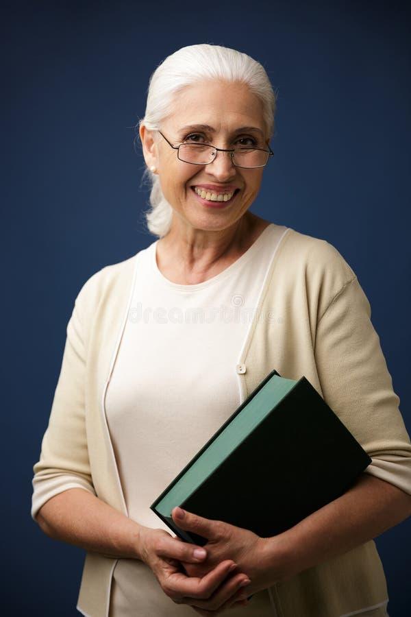 快乐的年迈的妇女画象玻璃的,拿着书, lookin 免版税库存照片