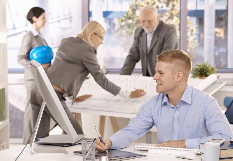 快乐的建筑师小组在办公室 免版税库存图片