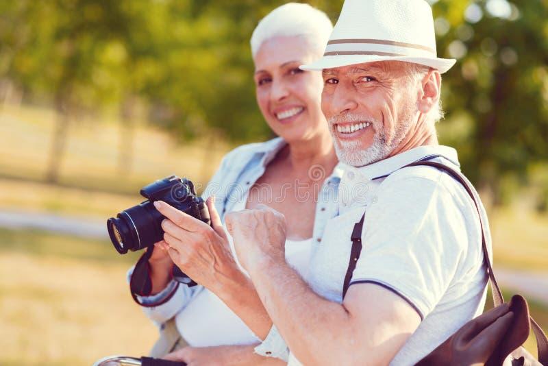 快乐的微笑丈夫和的妻子,当看家庭照片时 免版税库存照片
