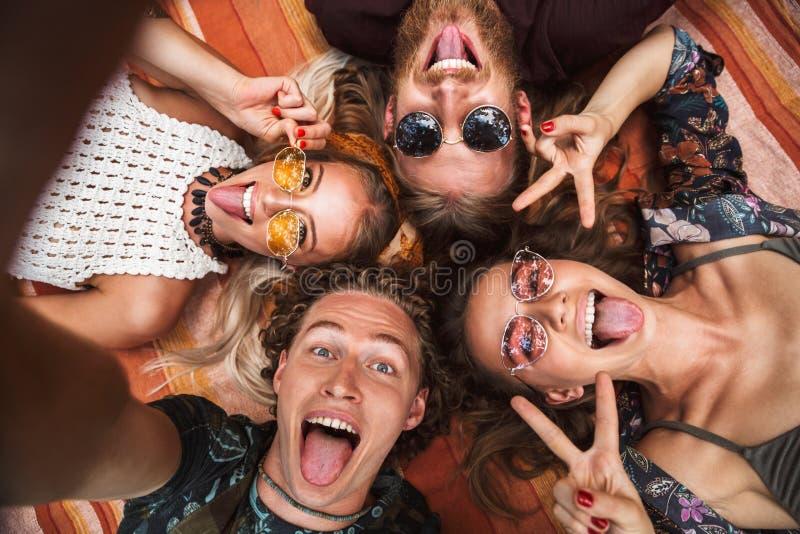 快乐的微笑和说谎在b的嬉皮男人和妇女画象  免版税库存照片