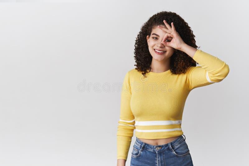 快乐的微笑的吸引人西班牙年轻卷发的深色的女生展示okay ok标志眼睛没有问题容易地 免版税库存照片