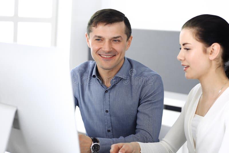 快乐的微笑的商人和妇女与计算机一起使用在现代办公室 在见面或工作场所的特写 免版税库存图片