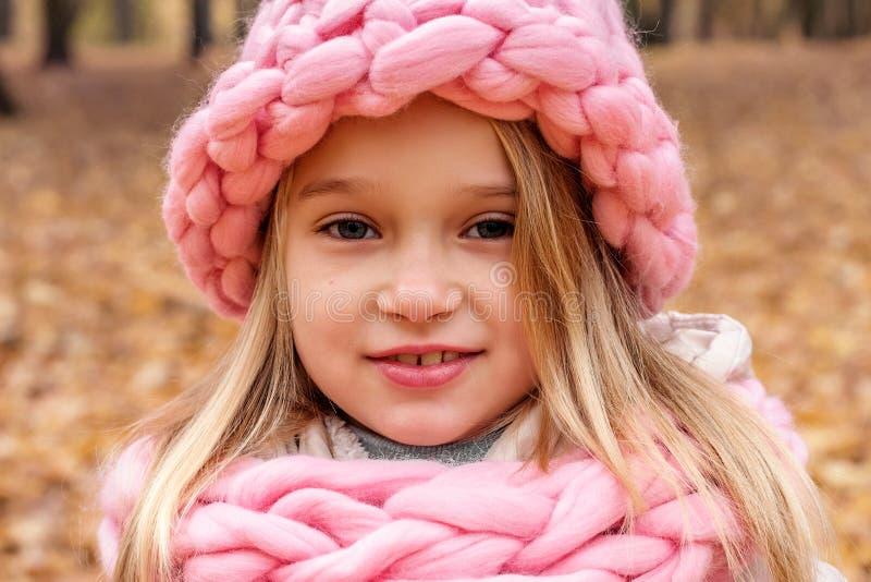 快乐的微笑的女孩特写镜头画象在帽子和围巾粗糙的手工编织的圣诞节冬天 免版税库存图片