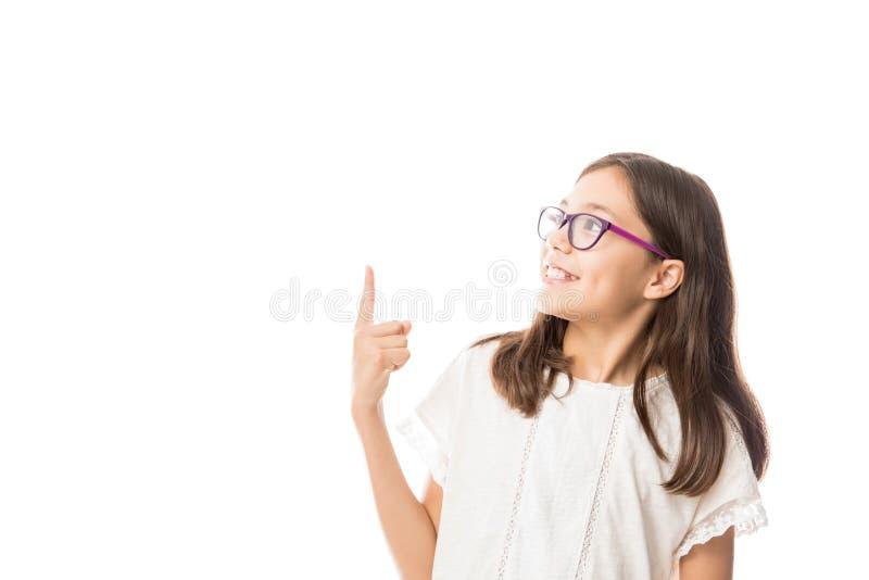 快乐的微笑的女孩画象指向手和手指由s决定 免版税库存图片