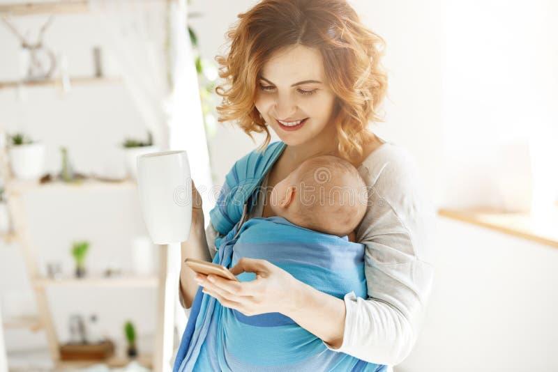 快乐的微笑的母亲喝可可粉和发短信给她心爱的丈夫,当打盹在婴孩的小儿子亭亭玉立时 大气  免版税库存照片