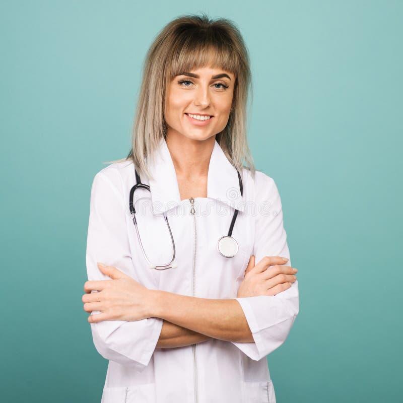 快乐的愉快的医生用在蓝色背景的横渡的手 免版税图库摄影
