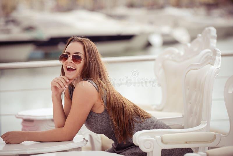快乐的愉快的微笑的美丽的女性在豪华小游艇船坞背景的餐馆 免版税库存照片
