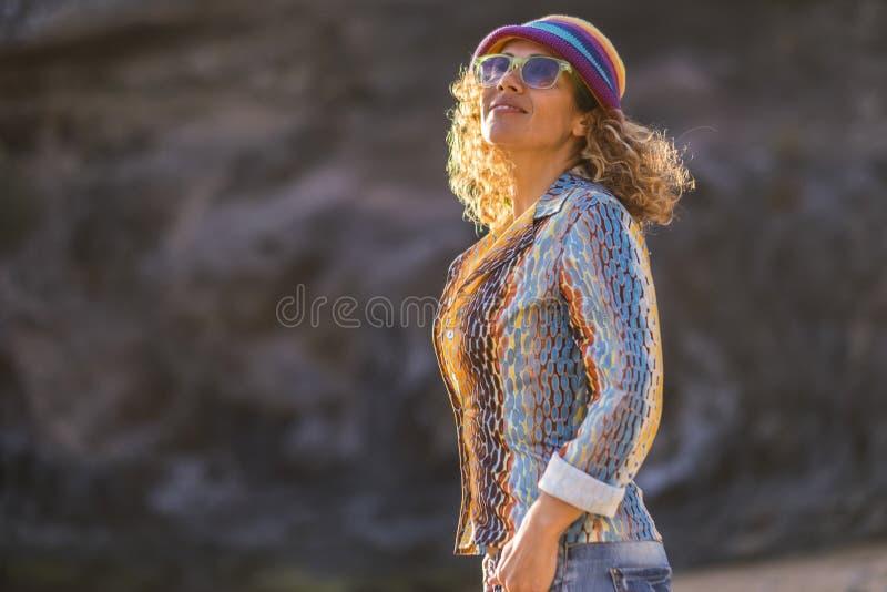 快乐的愉快的有吸引力的中年白种人妇女微笑和神色在享用好的天气和太阳的天空中 ?? 免版税库存图片