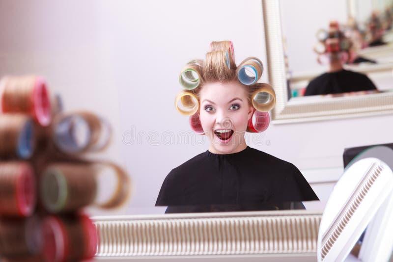快乐的愉快的白肤金发的女孩卷发夹路辗美发师美容院 免版税库存图片