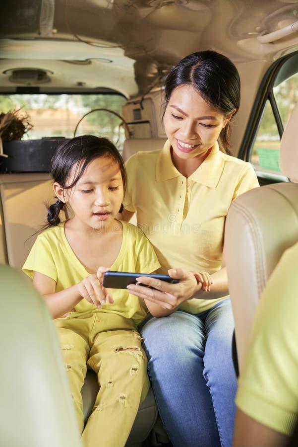 快乐的打在智能手机的母亲和女儿比赛 图库摄影