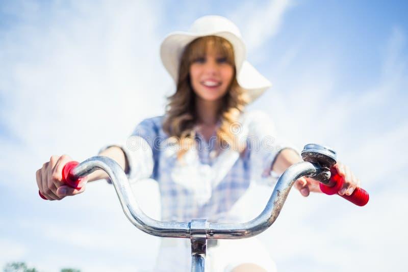 快乐的时髦白肤金发的骑马她的自行车 免版税库存照片