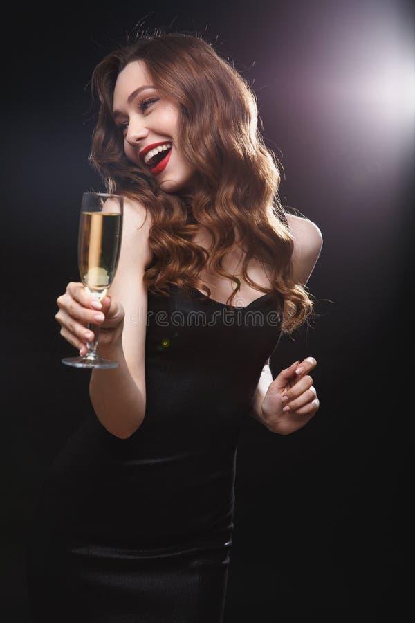 快乐的有吸引力的少妇饮用的香槟和有乐趣 免版税库存图片