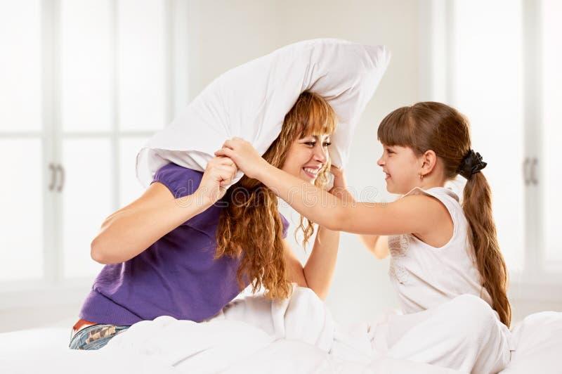 快乐的有母亲和的女儿枕头战 免版税库存图片