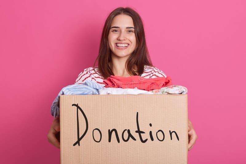 快乐的有用的志愿身分被隔绝在桃红色背景在演播室,拿着有题字捐赠的箱子,有很多  库存照片