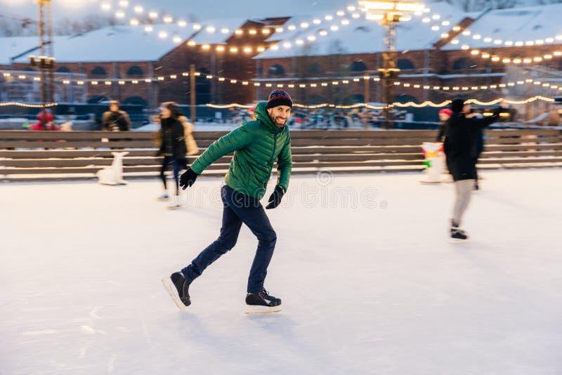 快乐的有胡子的人实践去滑冰在冰圆环,有chee 免版税库存图片
