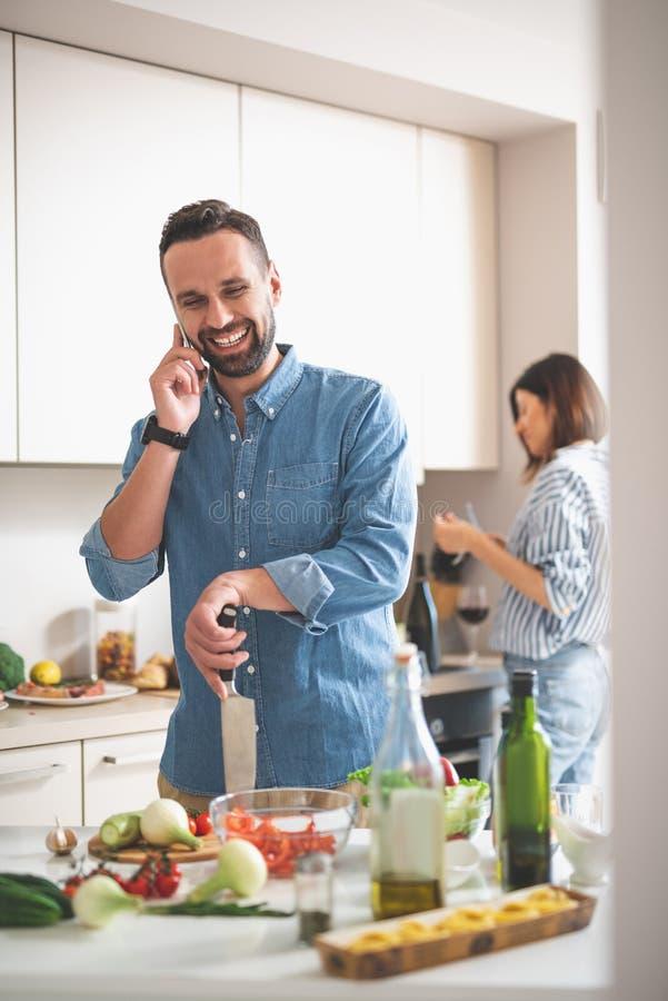 快乐的有胡子的人谈话在手机在厨房里 免版税库存图片