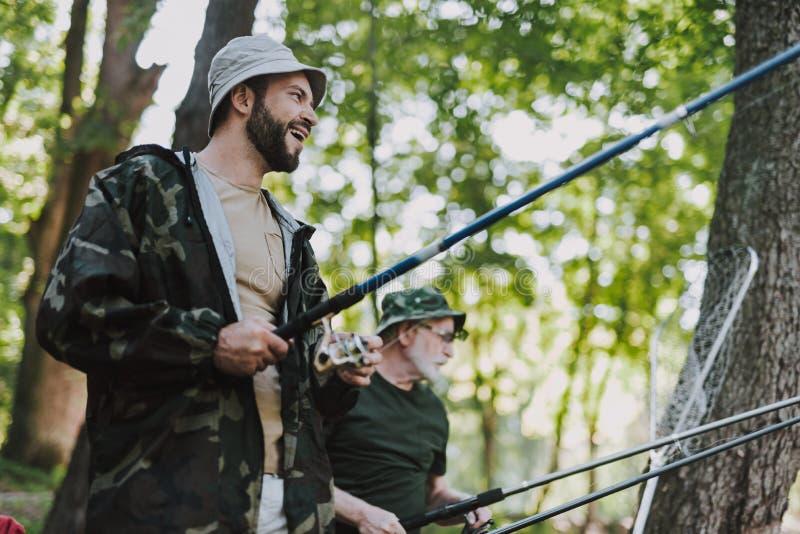 快乐的有胡子的人钓鱼的低角度 图库摄影