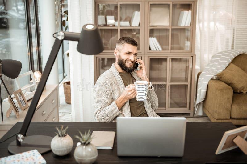 快乐的正面人谈话在手机和饮用的热的茶 图库摄影