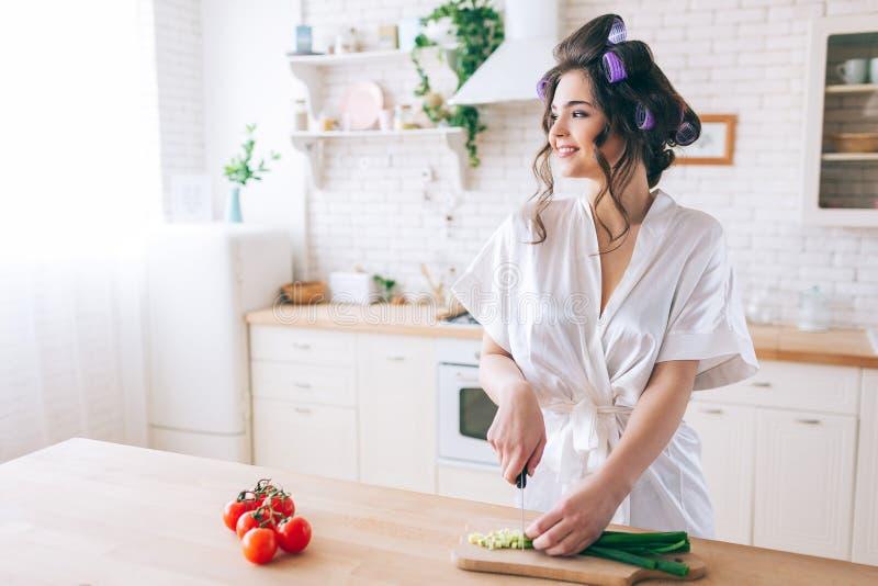 快乐的正面年轻女人立场在厨房里和看看窗口 切在书桌上的大葱 女性管家穿戴 免版税库存图片