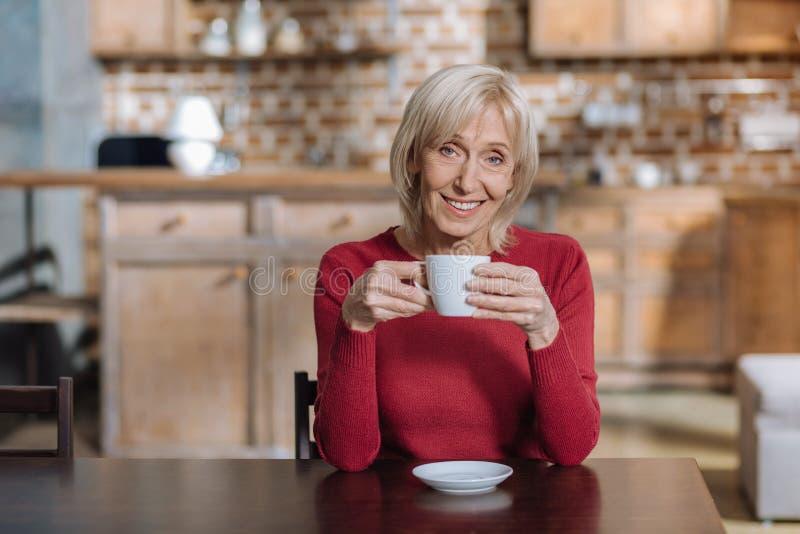 快乐的正面资深妇女饮用的茶和微笑 免版税库存照片