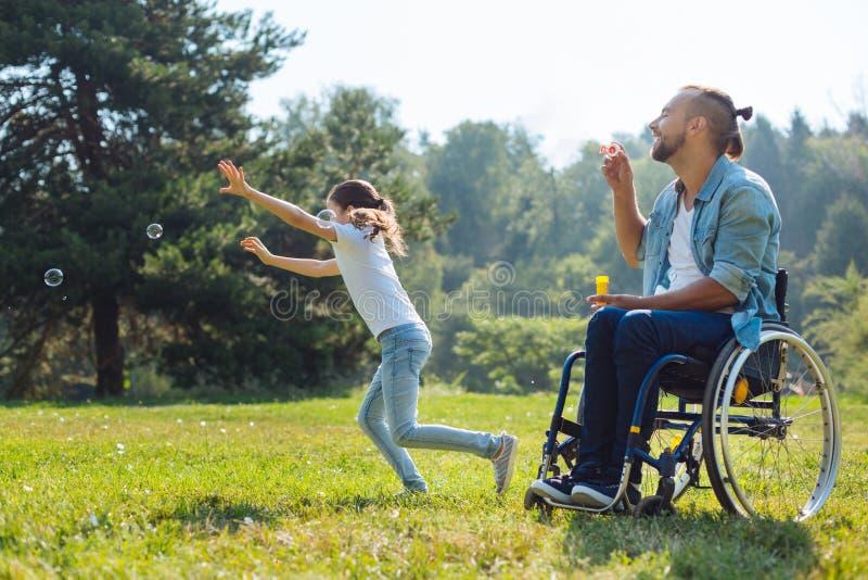 快乐的残疾使用与肥皂泡的父亲和女儿 库存图片
