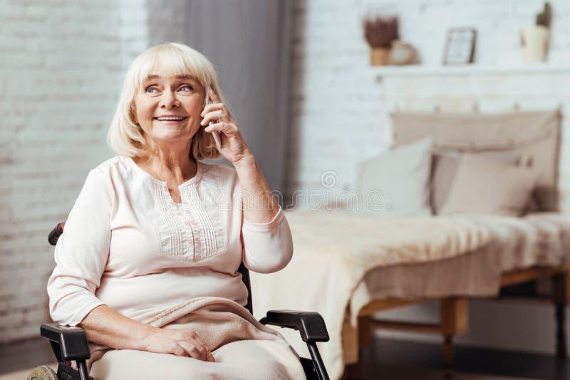 快乐的残疾资深妇女谈话在巧妙的电话 免版税库存图片