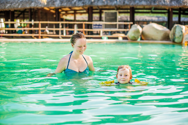年轻快乐的母亲和儿子游泳池的 库存照片