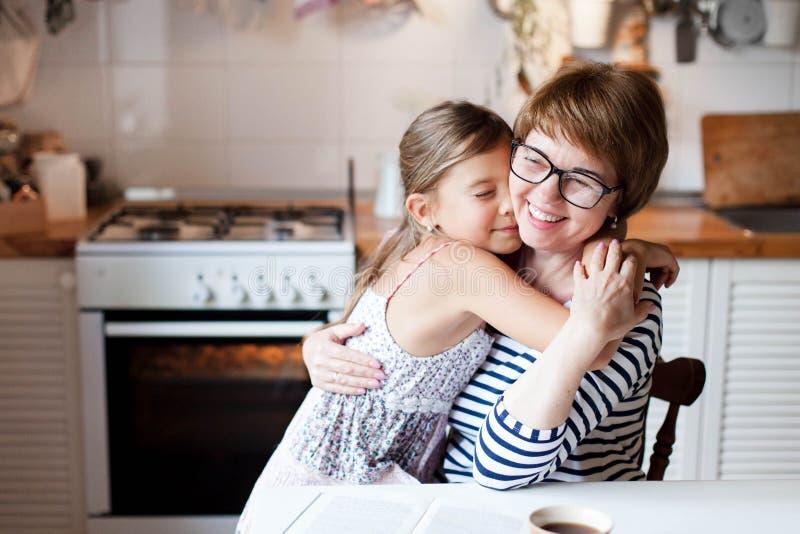 快乐的母亲拥抱女儿在舒适的家庭厨房 女人和可爱的小女孩在笑 免版税图库摄影