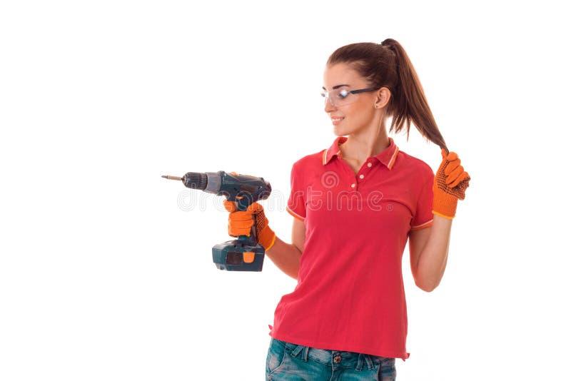 快乐的深色的妇女建造者在白色背景做整修与操练她的被隔绝的手 库存照片