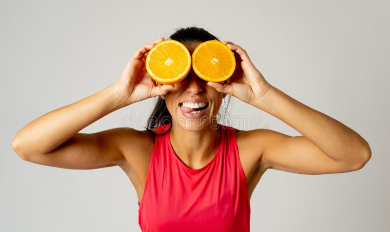 快乐的滑稽和有吸引力的妇女藏品画象切了在她的眼睛的桔子 库存照片