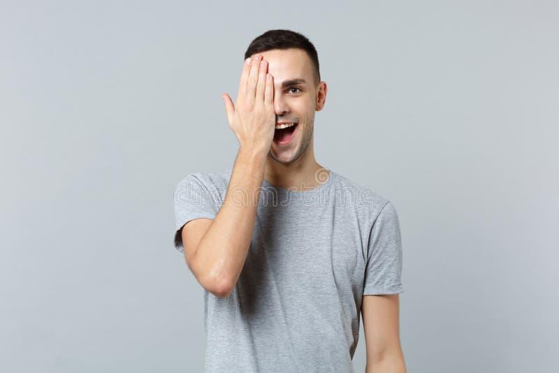 快乐的滑稽的年轻人画象保留嘴开放盖的面孔用手的便服的隔绝在灰色 免版税库存照片