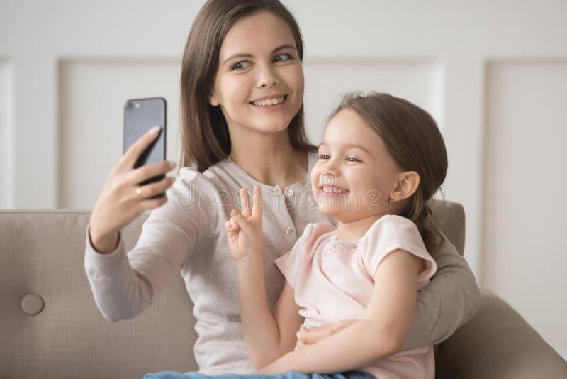 快乐的滑稽的母亲拿着智能手机与女儿的作为selfie 免版税库存照片