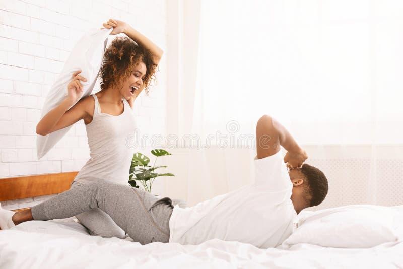 快乐的爱恋的夫妇由枕头在床上战斗 图库摄影