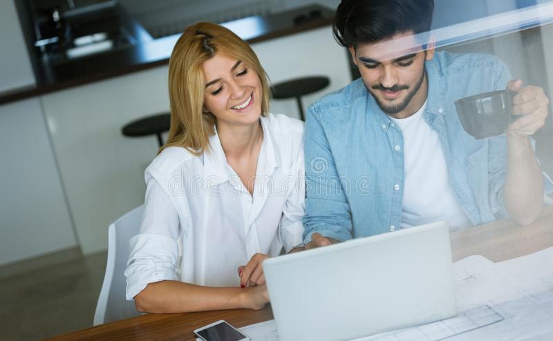 快乐的爱恋的年轻夫妇照片使用膝上型计算机的 图库摄影