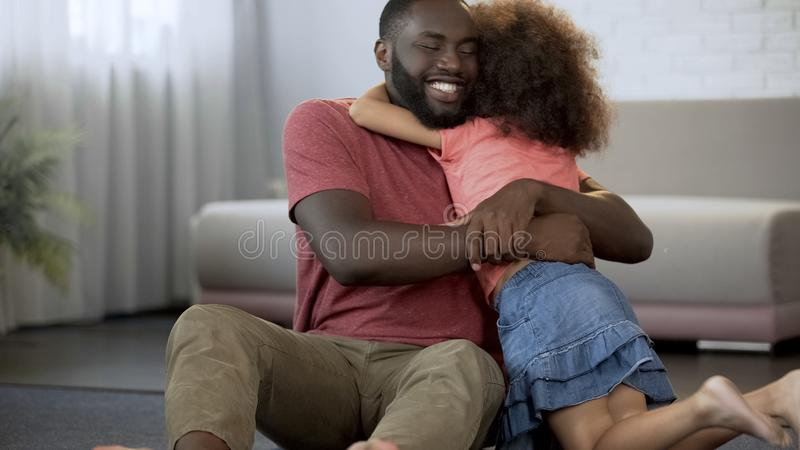 快乐的父亲拥抱受爱护的女儿,在家庭的优秀关系 免版税库存照片