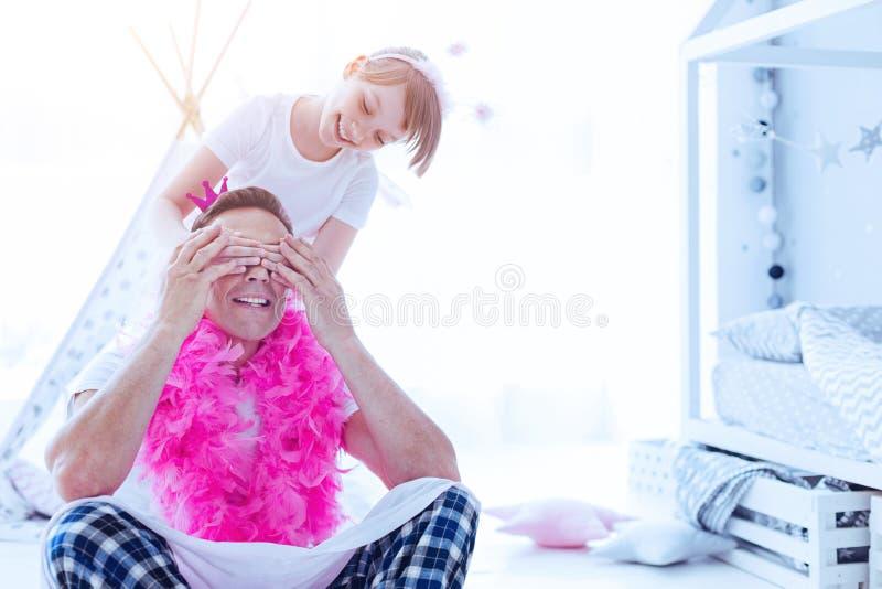 快乐的爸爸的女孩闭合值的眼睛,当使用时 免版税库存照片
