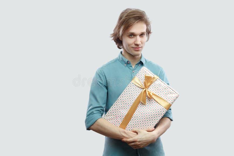 快乐的现代年轻人画象浅兰的衬衣身分和拿着的一个礼物与黄色弓,看照相机和 免版税库存图片