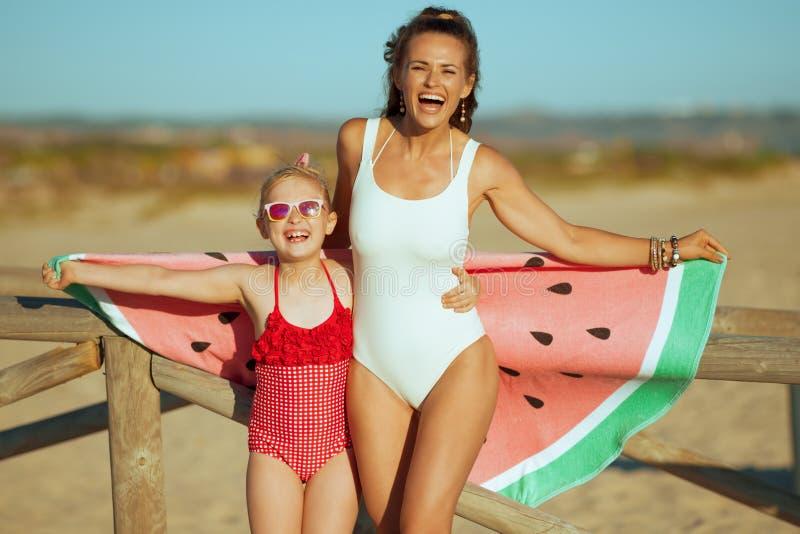 快乐的现代拿着滑稽的西瓜毛巾的母亲和孩子 免版税库存图片